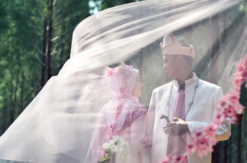 Creative photo shoot of a malay loving couple bride and groom royalty free stock images