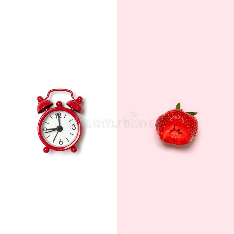 Creative picture of red alarm clock and red strawberry royalty free stock image
