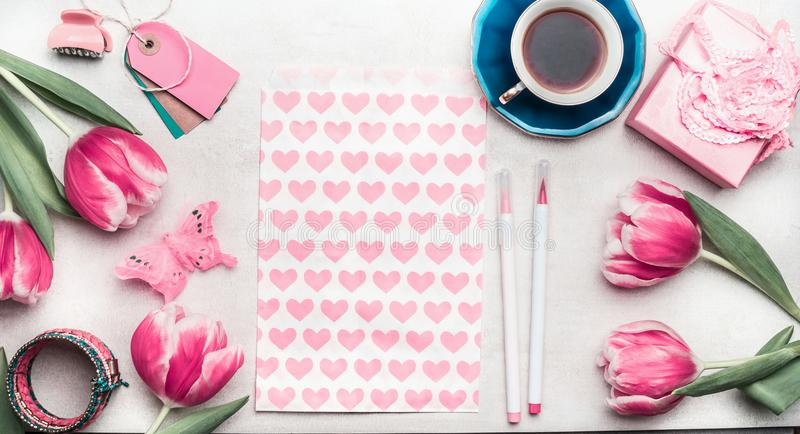 Creative pink mock up with tulips, paper package with hearts, marker pen, tags and cup of coffee on desktop, top view, frame. royalty free stock image