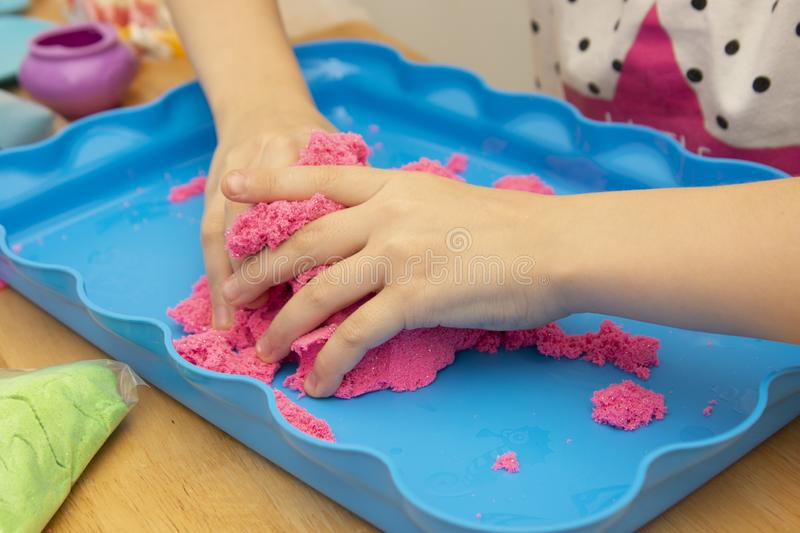 Creative play for children. Education and parenting. Children playing with pink kinetik sand royalty free stock photos