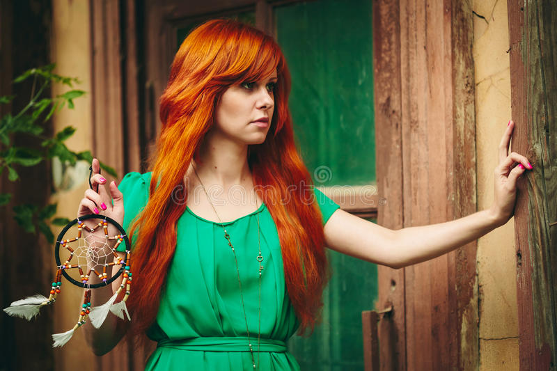 Creative Portrait of Redhead Woman in Green Dress. Creative Portrait of Redhead Young Woman in Green Dress with DreamCatcher in her Hands. Long Beautiful Red stock photography