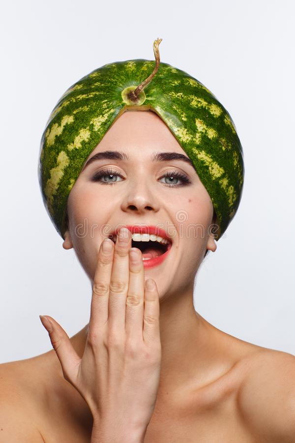Creative portrait of a woman with a watermelon on her head instead of a hat. White background. Studio photo session royalty free stock photo