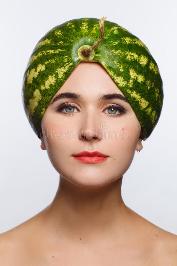 Creative portrait of a woman with a watermelon on her head instead of a hat. White background. Studio photo session royalty free stock photos