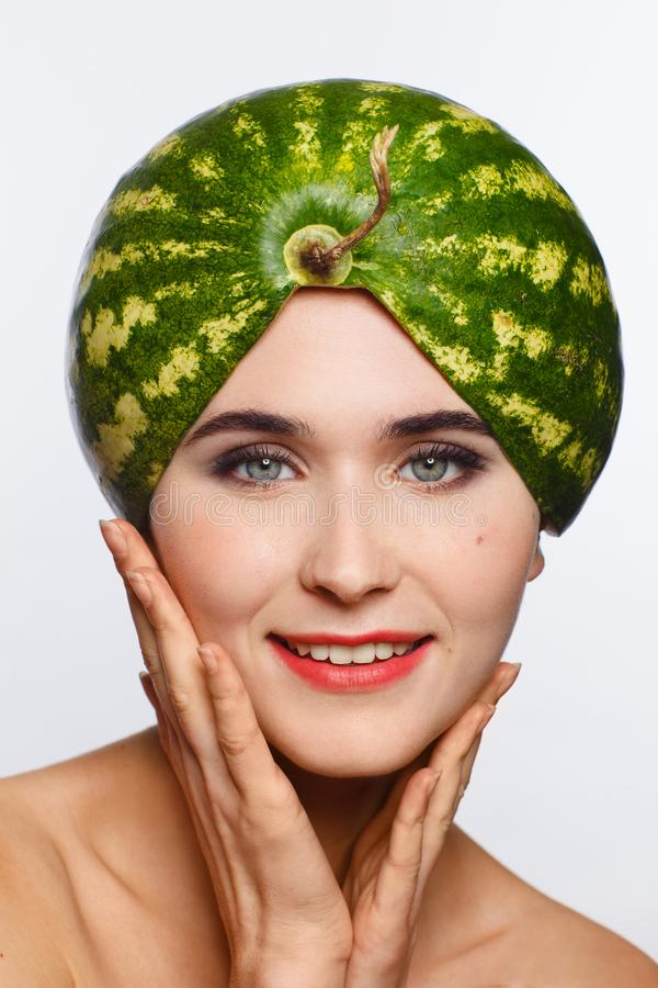 Creative portrait of a woman with a watermelon on her head instead of a hat. White background. Studio photo session royalty free stock photography