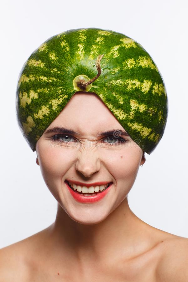 Creative portrait of a woman with a watermelon on her head instead of a hat. White background. Studio photo session stock photos