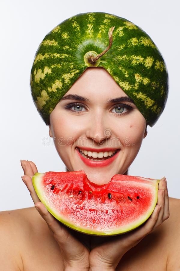 Creative portrait of a woman with a watermelon on her head and in her hands. White background. Studio photo session royalty free stock image