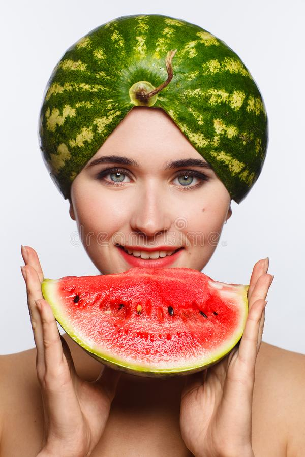 Creative portrait of a woman with a watermelon on her head and in her hands. White background. Studio photo session royalty free stock photo