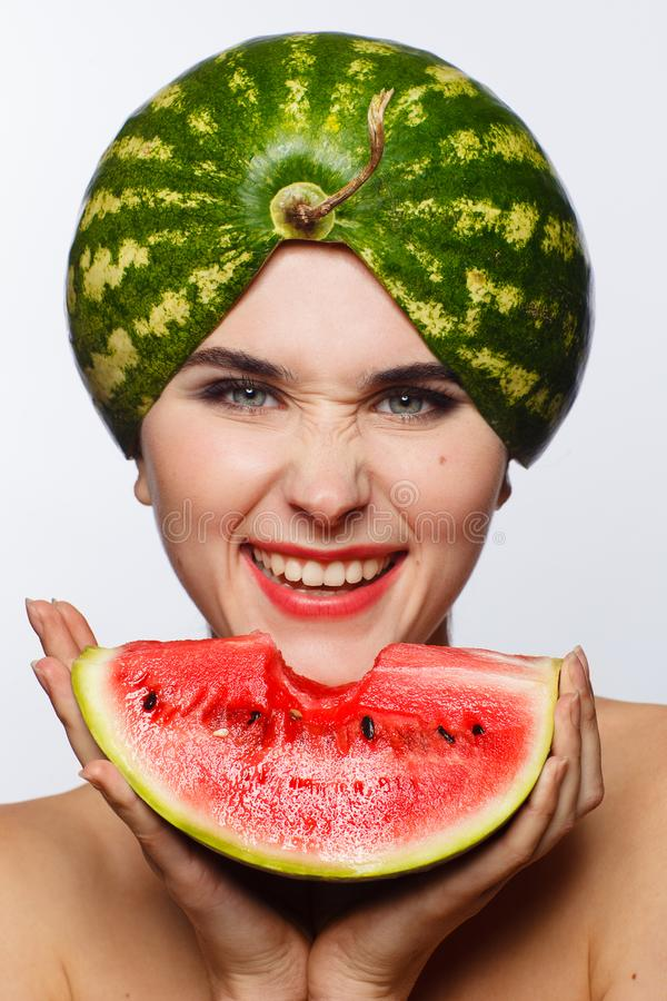 Creative portrait of a woman with a watermelon on her head and in her hands. White background. Studio photo session royalty free stock photography