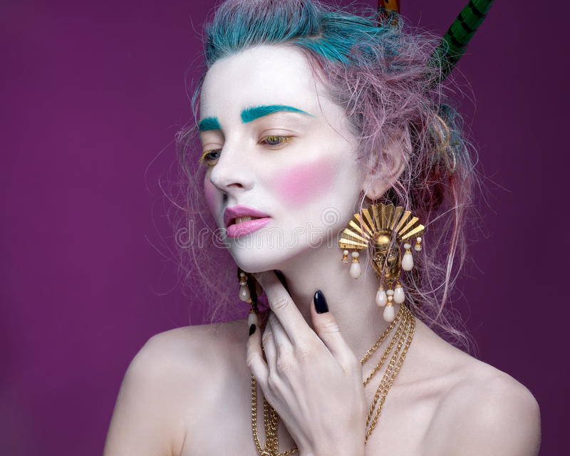 Creative portrait of young woman with artistic make-up. With bright colors in her hair and a white face stock photography