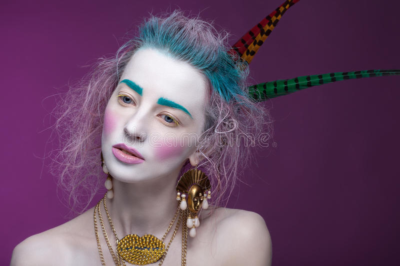 Creative portrait of young woman with artistic make-up. With bright colors in her hair and a white face stock photos
