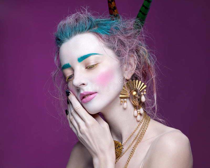 Creative portrait of young woman with artistic make-up. With bright colors in her hair and a white face stock photo