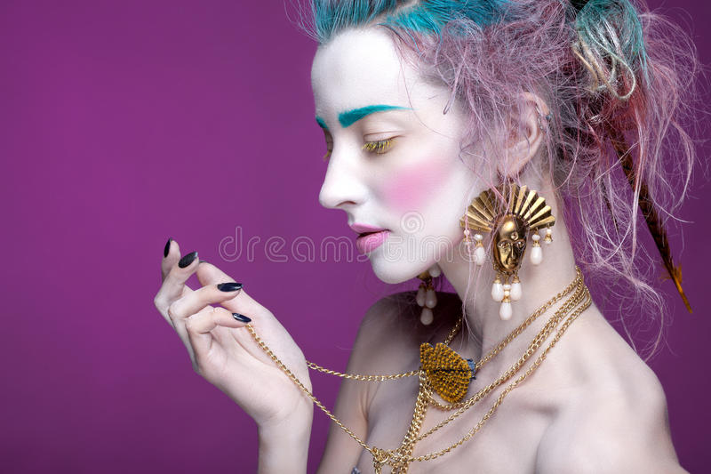 Creative portrait of young woman with artistic make-up. With bright colors in her hair and a white face royalty free stock photography