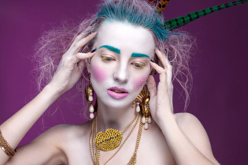 Creative portrait of young woman with artistic make-up. With bright colors in her hair and a white face stock image