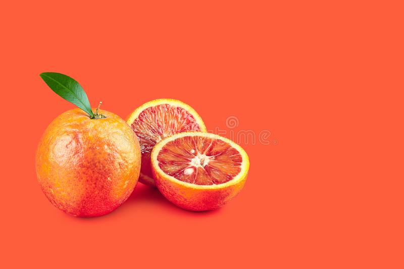 Creative poster with halfed and sicilian orange isolated on living coral background. Copy space for design. Concept. Creative poster with halfed and sicilian royalty free stock images