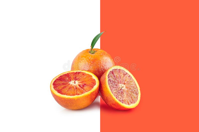 Creative poster with halfed and sicilian orange isolated on white and living coral background. Copy space for design. Concept. Creative poster with halfed and royalty free stock photo