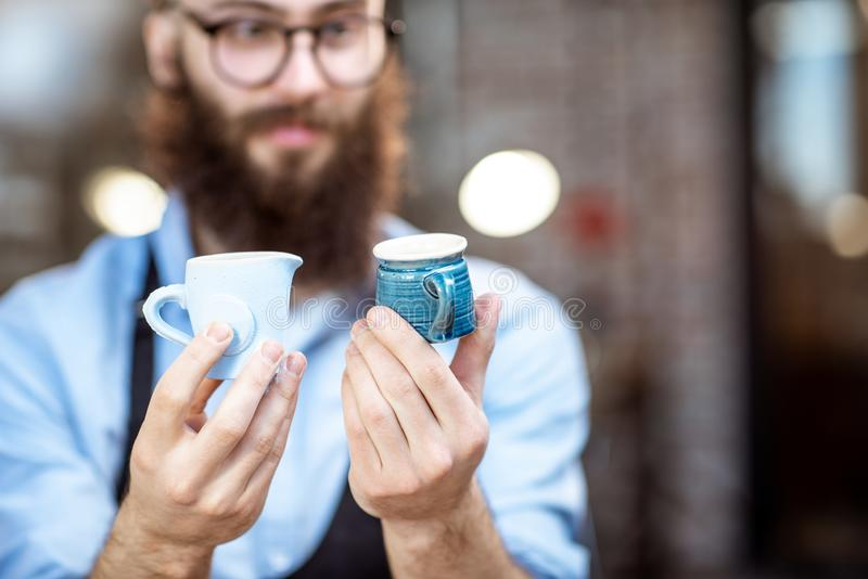 Creative potter with ceramics at the pottery shop. Portrait of a creative bearded potter man holding ceramic products at the pottery shop royalty free stock image