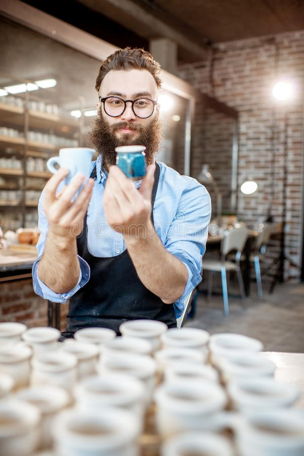 Creative potter with ceramics at the pottery shop. Portrait of a creative bearded potter man holding ceramic products at the pottery shop stock photo
