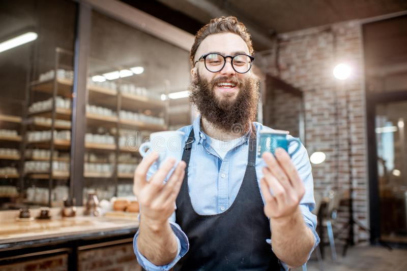 Creative potter with ceramics at the pottery shop. Portrait of a creative bearded potter man holding ceramic products at the pottery shop stock image