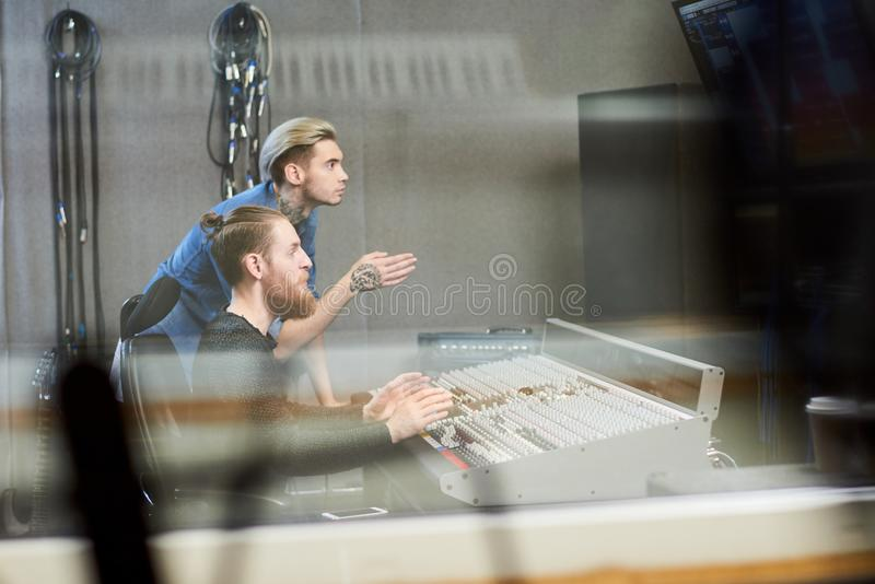 Creative producers making music in studio. Side view through glass of creative operators sitting at music console in recording studio and talking to singer stock photos