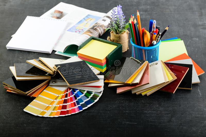 Creative professional designer workplace in the office. Pencils, material samples, journal and color charts on dark. Table, concept of design project stock photo