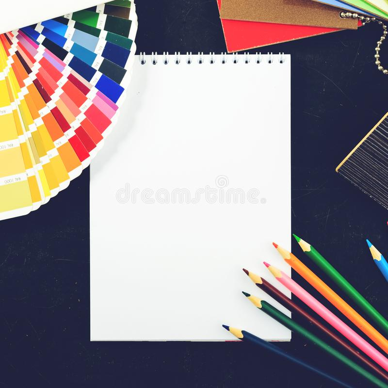 Creative professional modern designer workplace in the office. C. Lose-up top view of open notebook, pencils, material samples and color charts on dark table stock photography