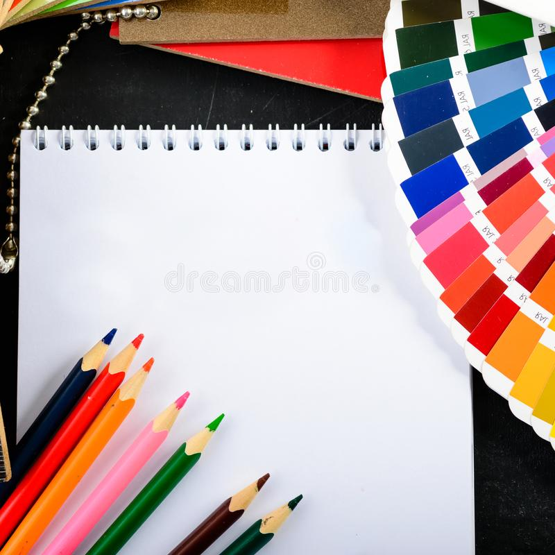 Creative professional modern designer workplace in the office. C. Lose-up top view of open notebook, colorful pencils and color charts on dark table, concept of royalty free stock photos