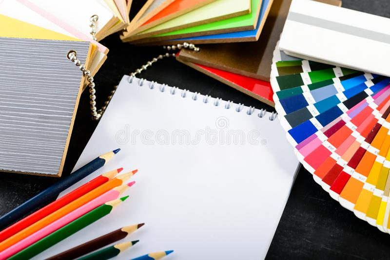 Creative professional modern designer workplace in the office. O. Pen notebook, pencils, material samples and color charts on dark table, concept of choosing stock photo