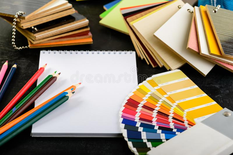 Creative professional modern designer workplace in the office. O. Pen notebook, pencils, material samples and color charts on dark table, concept of choosing royalty free stock image
