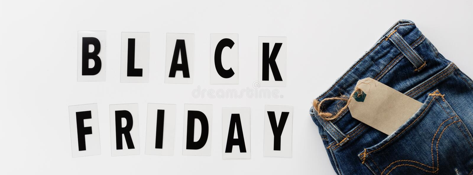 Creative promotion composition Black friday text and jeans on white background. Flat lay, top view, overhead, mockup, template. Creative promotion composition stock image