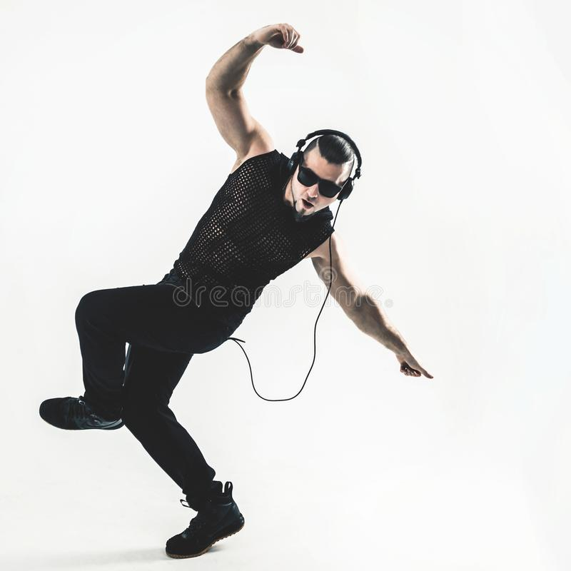 Creative rapper in the headphones and dark glasses performs a ra. P song to break dancing .photo on a white background and has an empty space for your text royalty free stock image