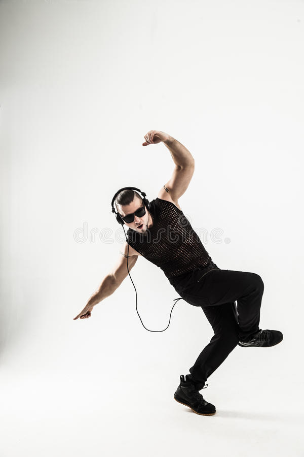 Creative rapper in the headphones and dark glasses performs a ra. P song to break dancing .photo on a white background and has an empty space for your text stock photography