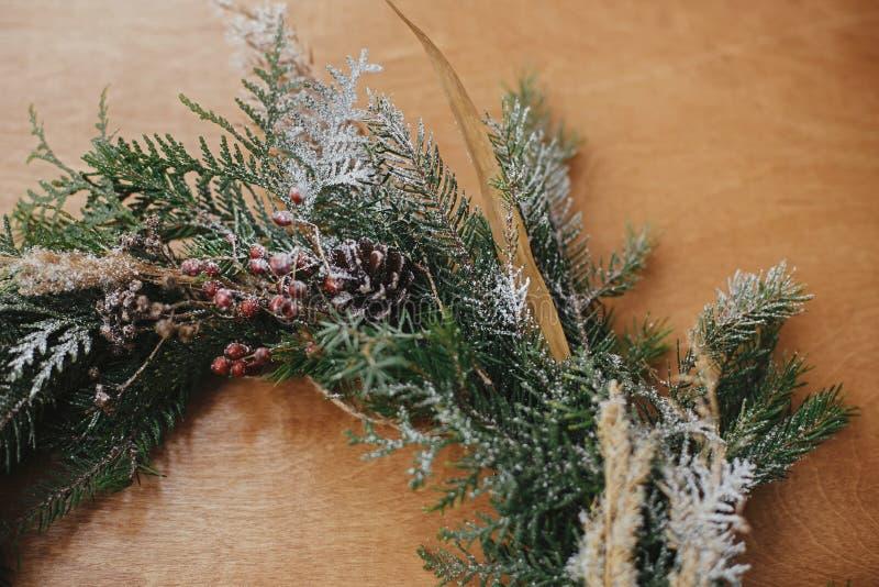 Creative rustic christmas wreath close on wood table Pormenores da coroa de natal com ramos de abeto, bagas, pinhões e pinheiros imagem de stock royalty free