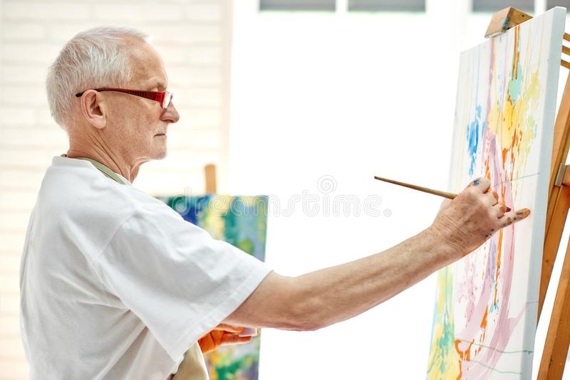 Creative senior painter drawing colorful picture at bright studio. Side view of painting process in art workplace. Male artist wearing in white t-shirt and stock photos