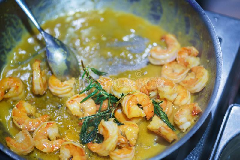 Creative serving of seafood during at event. Top view on cooked shrimps in a sauce in a pan. Asian cuisine. Catering.  Soft focus royalty free stock photography