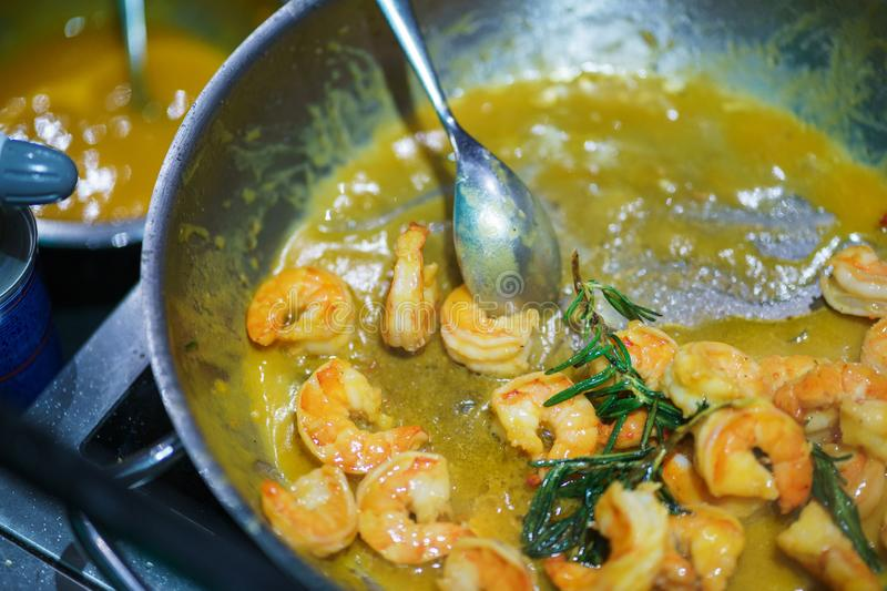 Creative serving of seafood during at event. Top view on cooked shrimps in a sauce in a pan. Asian cuisine. Catering.  Soft focus stock images