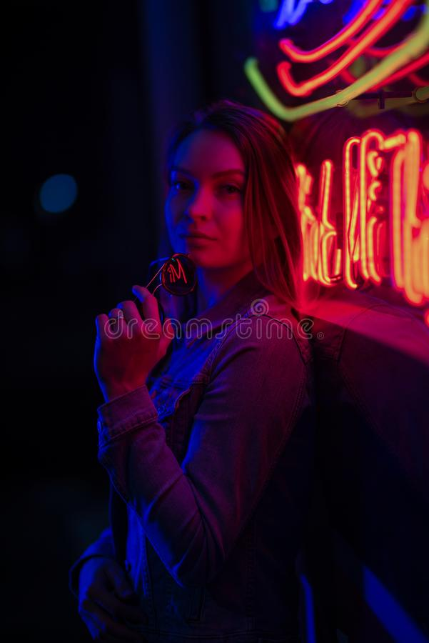 Creative sexual portrait of a girl in neon lighting with glasses stock photos