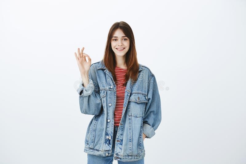 Creative smart girl showing she can deal with anything. Portrait of happy carefree confident woman in stylish denim stock photography