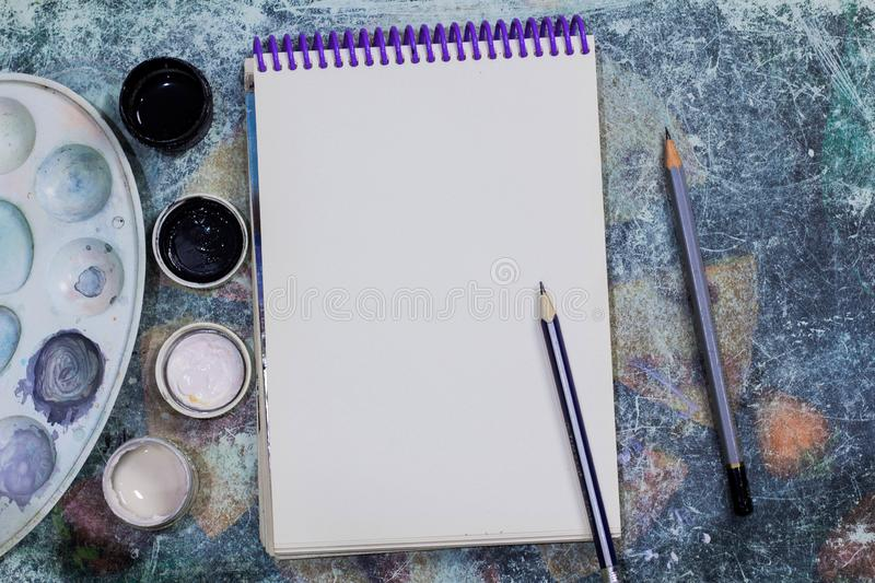 Creative space. The working space of the artist on the shabby table: paint gouache, notebook, pencils royalty free stock photos