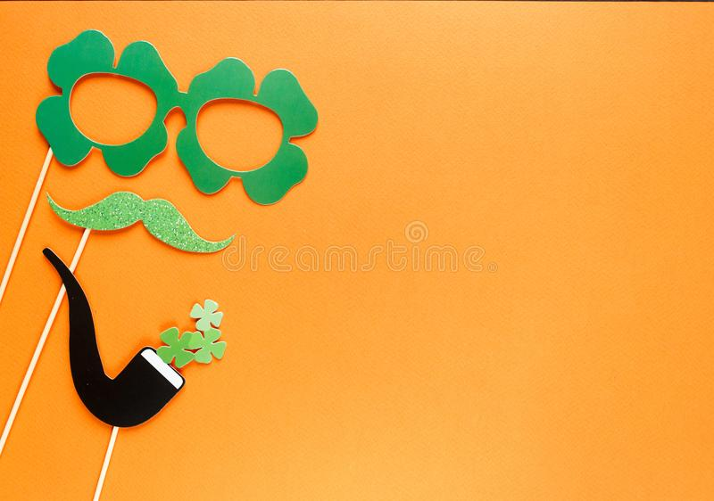Creative st Patricks Day orange background. Flat lay composition of Irish holiday celebration with photo booth decor: hat, glasses royalty free stock photos