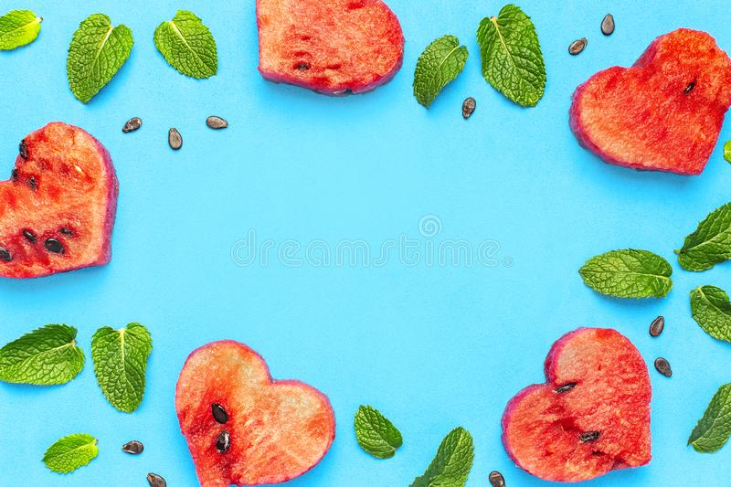 Creative summer food concept. Frame of Juicy slices of ripe red watermelon in the shape of a heart and mint leaves on blue. Background. Flat lay, top view, copy stock photo