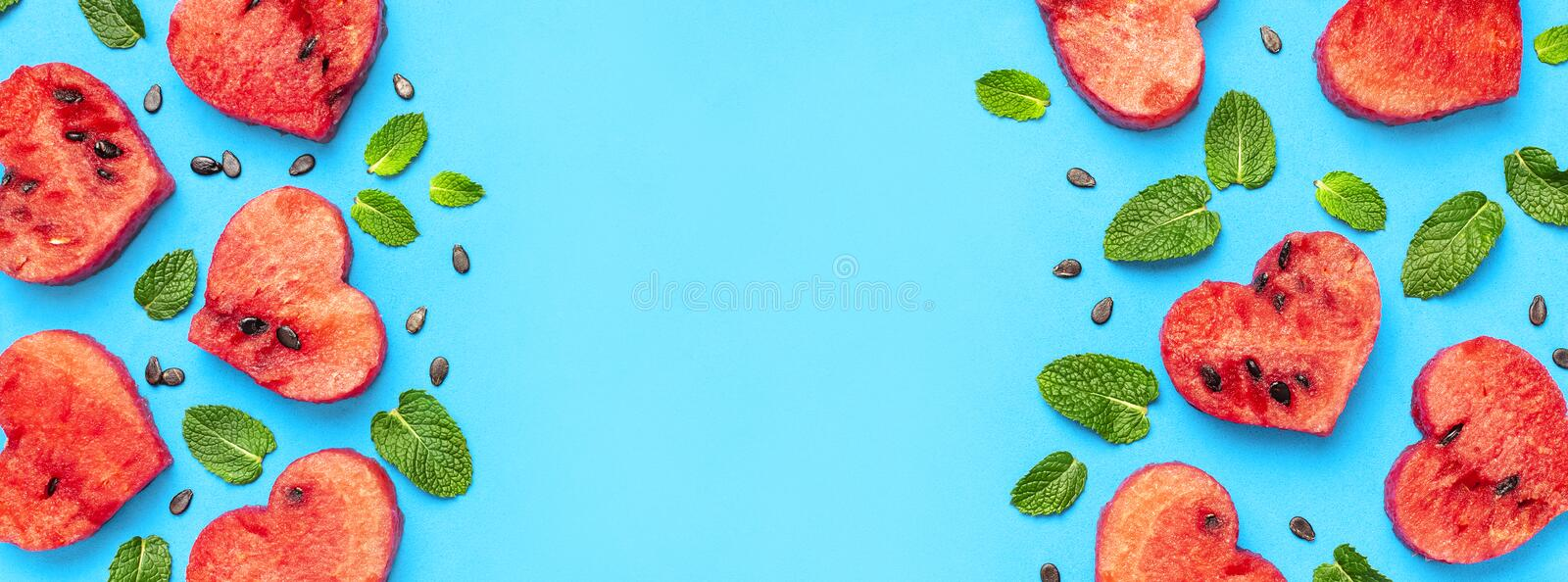 Creative summer food concept. Frame of Juicy slices of ripe red watermelon in the shape of a heart and mint leaves on blue. Background. Flat lay, top view, copy royalty free stock image