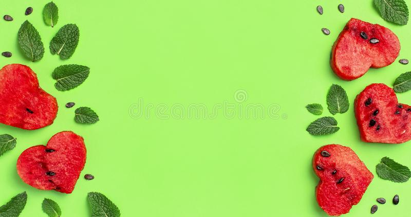 Creative summer food concept. Frame of Juicy slices of ripe red watermelon in the shape of a heart and mint leaves on green. Background. Flat lay, top view stock photography