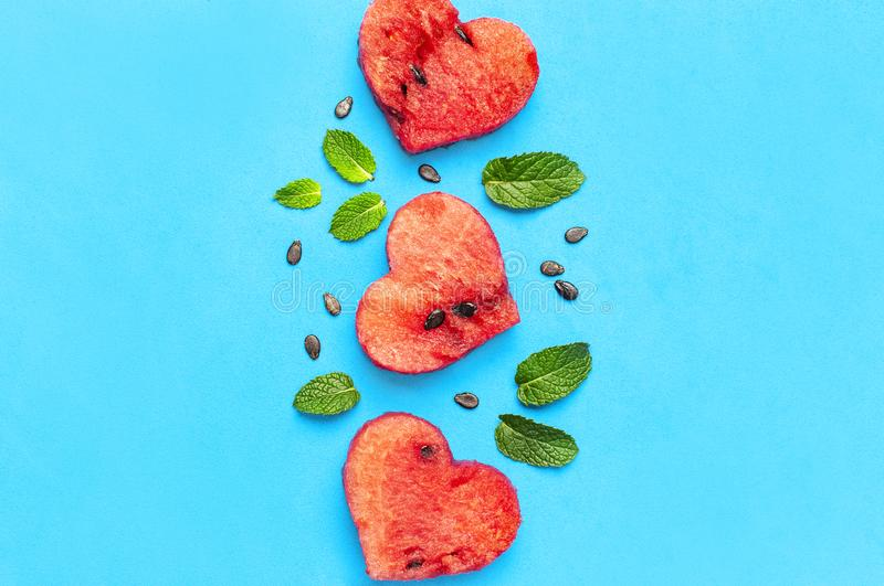 Creative summer food concept. Juicy slices of ripe red watermelon in the shape of a heart and mint leaves on blue background. Flat. Lay, top view, copy space stock photo