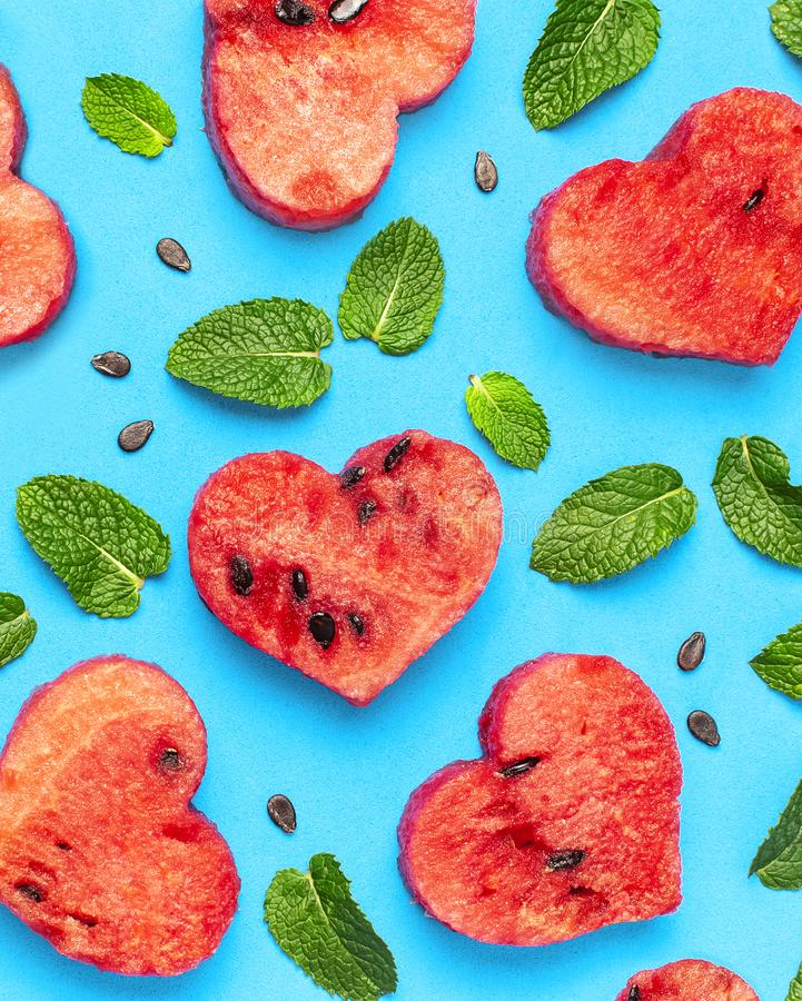 Creative summer food concept. Juicy slices of ripe red watermelon in the shape of a heart and mint leaves on blue background. Flat. Lay, top view, copy space stock photography