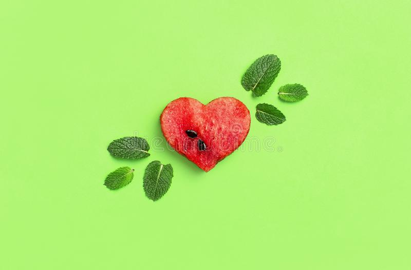 Creative summer food concept. Juicy slices of ripe red watermelon in the shape of a heart and mint leaves on green background. Flat lay, top view, copy space royalty free stock photo