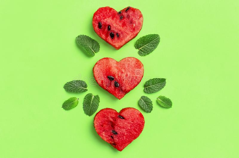 Creative summer food concept. Juicy slices of ripe red watermelon in the shape of a heart and mint leaves on green background. Flat lay, top view, copy space stock photos