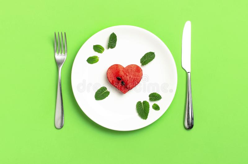 Creative summer food concept. Juicy slices of ripe red watermelon in the shape of a heart and mint leaves in white plate, knife,. Fork on green background. Flat royalty free stock image
