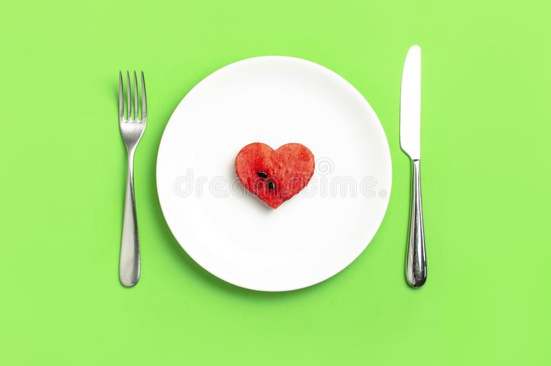 Creative summer food diet concept. Juicy slices of ripe red watermelon in the shape of a heart in white plate, knife, fork on. Green background. Flat lay top stock photos