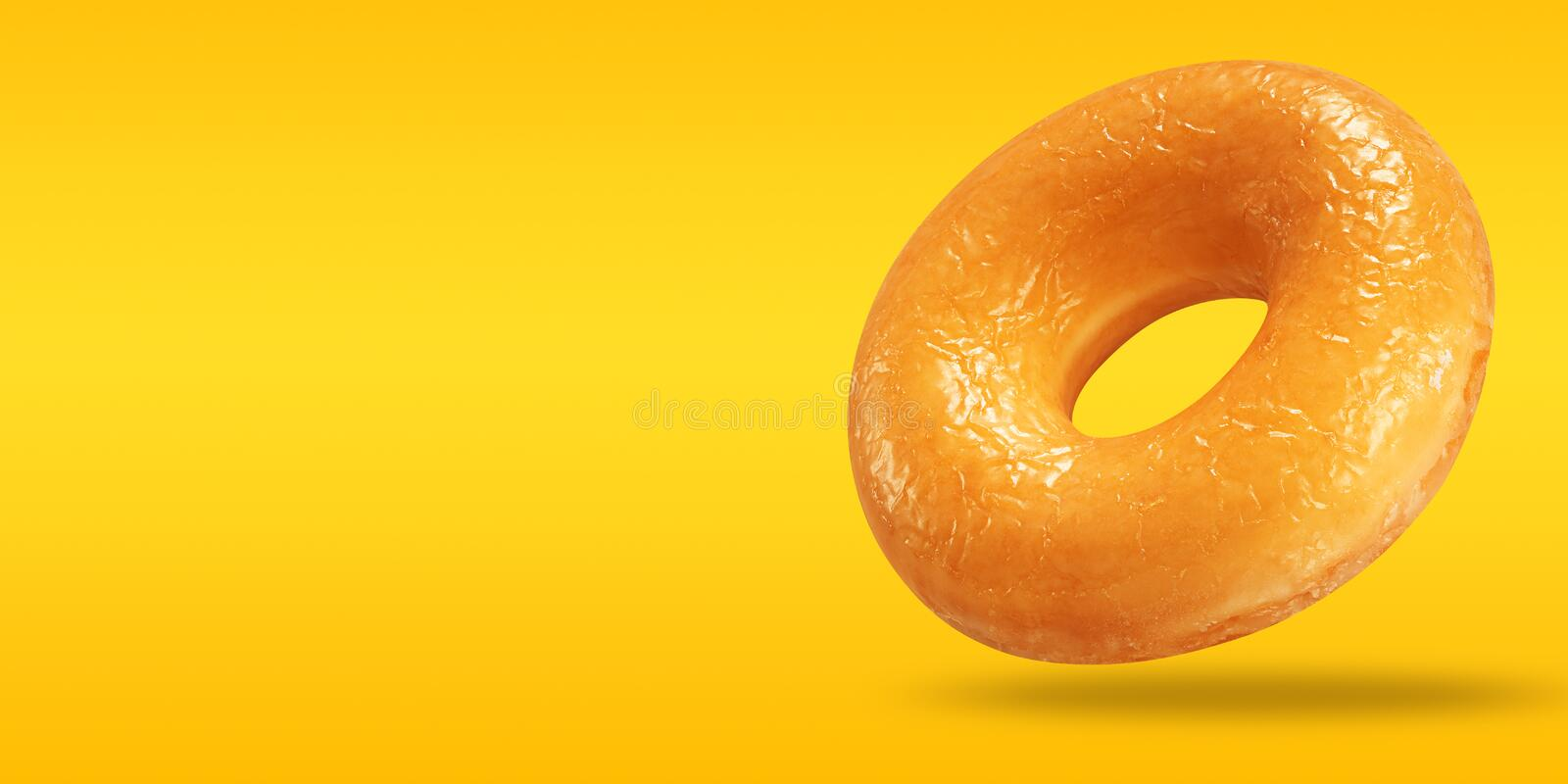 Creative sweet food concept. Donut glazed with copy space on pastel yellow and orange background.  royalty free stock photo