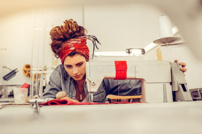 Creative tailoress sewing a dress in a studio. stock photo